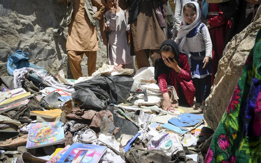 Children pick through items left behind the day after a deadly attack on the Syed Al-Shahda school in Kabul, Afghanistan, May 9, 2021.