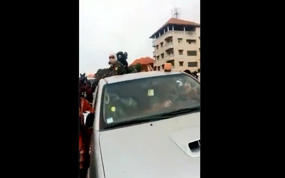 In a screenshot from a video posted on Twitter, a car carrying U.S. soldiers passes through a raucous crowd in the African country of Guinea. A coup there forced U.S. Africa Command to cancel a training event.