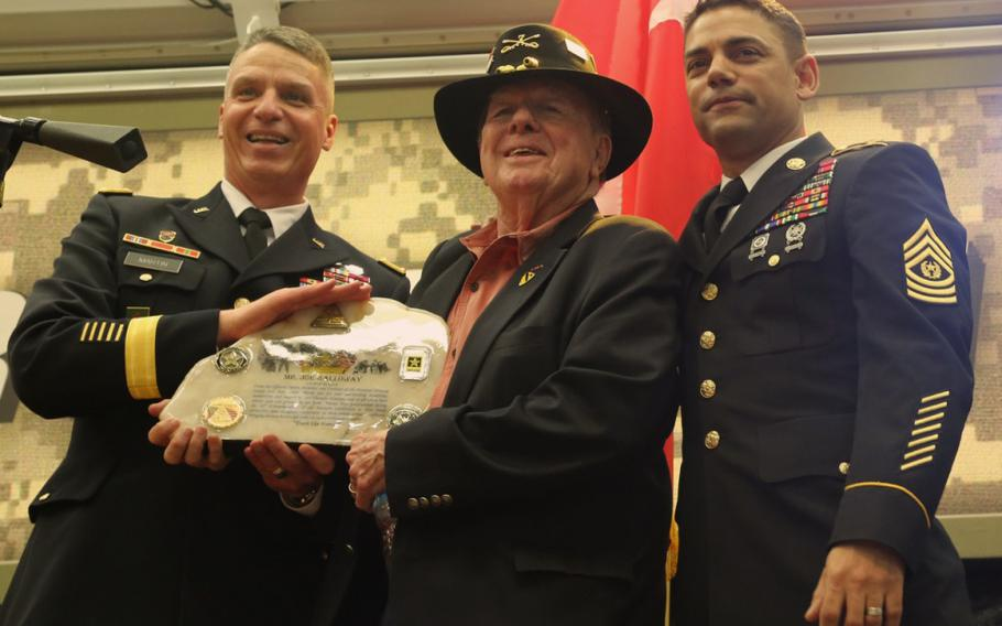 National Training Center Command Team, Maj. Gen. Joseph M. Martin and Command Sgt. Maj. Edison M. Rebuck present a gift to Joseph Galloway. Galloway was recognized with the Bronze Star with Valor when during the November 1965 Battle of Ia Drang, he repeatedly disregarded his own safety to rescue wounded soldiers under fire.