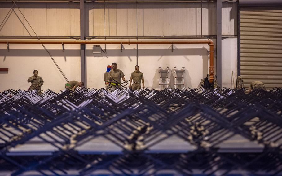 Service members assemble cots for Afghan evacuees Aug. 22, 2021, at Al Udeid Air Base, Qatar.