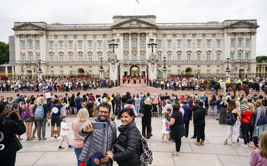 Members of the public watch the Changing of the Guard ceremony at Buckingham Palace, London, Monday August 23, 2021.