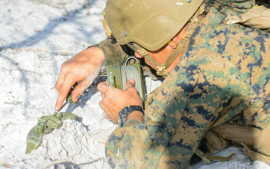 A Marine infantry student places a claymore mine during training at Camp Lejeune, N.C., on Aug. 27, 2021. The students were practicing an ambush during an initial infantry training pilot program meant to drastically change the way the Corps trains its infantrymen. The pilot program expands infantry training from nine to 14 weeks and places Marines in 14-person squads under a single instructor.