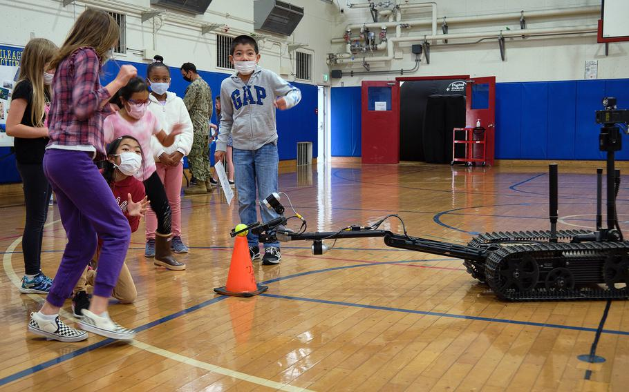 Lanham Elementary School students observe and control a robot used by Marine Corps explosive ordnance teams during a STEAM event at Naval Air Facility Atsugi, Japan, May 27, 2021.