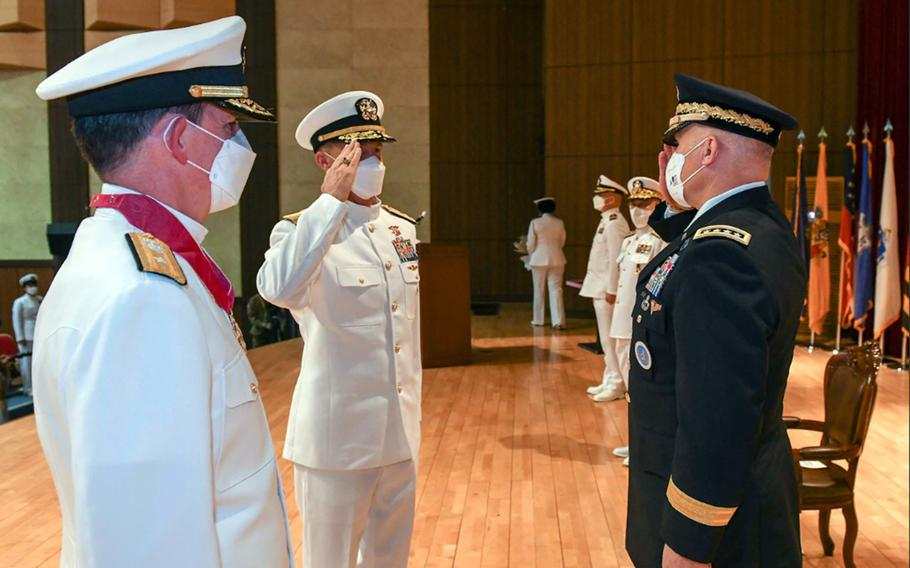 """Rear Adm. Mark Schafer, center, salutes the head of U.S. Forces Korea, Army Gen. Paul LaCamera, after taking command of Naval Forces Korea in Busan, South Korea, Sept. 29, 2021. The outgoing commander, Rear Adm. Michael """"Buzz"""" Donnelly, stands at left."""