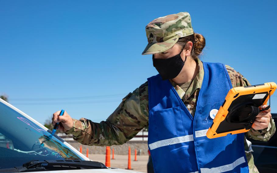 Army Sgt. Maggie Van Wagenen, a combat medic, writes a person's vaccination time on a car windshield June 4, 2021, at the Community Vaccination Center at the Colorado State Fairgrounds in Pueblo, Colo. The soldiers are a part of the federally supported vaccination mission that provides continued, flexible Department of Defense support to FEMA as part of the response to the coronavirus pandemic.