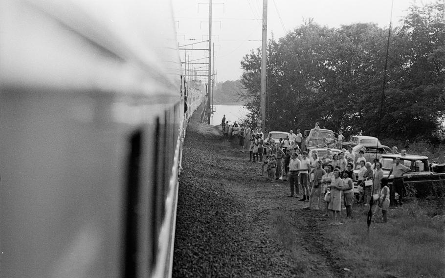 People stand near railroad tracks as a train carries the body of Robert F. Kennedy from New York to Washington, D.C., on June 8, 1968.