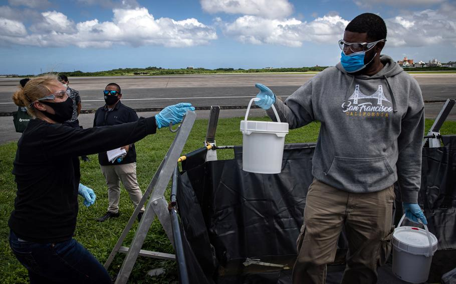 Japanese and U.S. military officials collect samples of treated wastewater at Marine Corps Air Station Futenma, Okinawa, July 19, 2021.