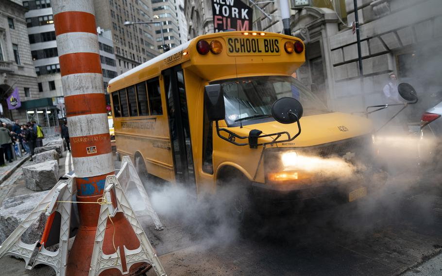 A school bus passes through a steam vent on a morning route, Monday, Oct. 4, 2021, in the Manhattan borough of New York.