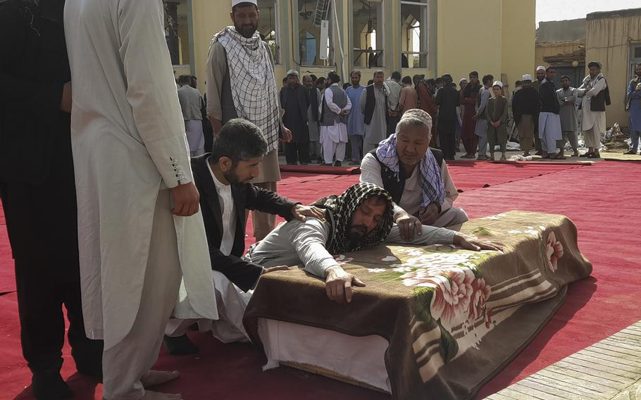 Relatives and residents attend a funeral ceremony for victims of a suicide attack at the Gozar-e-Sayed Abad Mosque in Kunduz, northern Afghanistan, Saturday, Oct. 9, 2021. The mosque was packed with Shiite Muslim worshippers when an Islamic State suicide bomber attacked during Friday prayers, killing dozens in the latest security challenge to the Taliban as they transition from insurgency to governance.