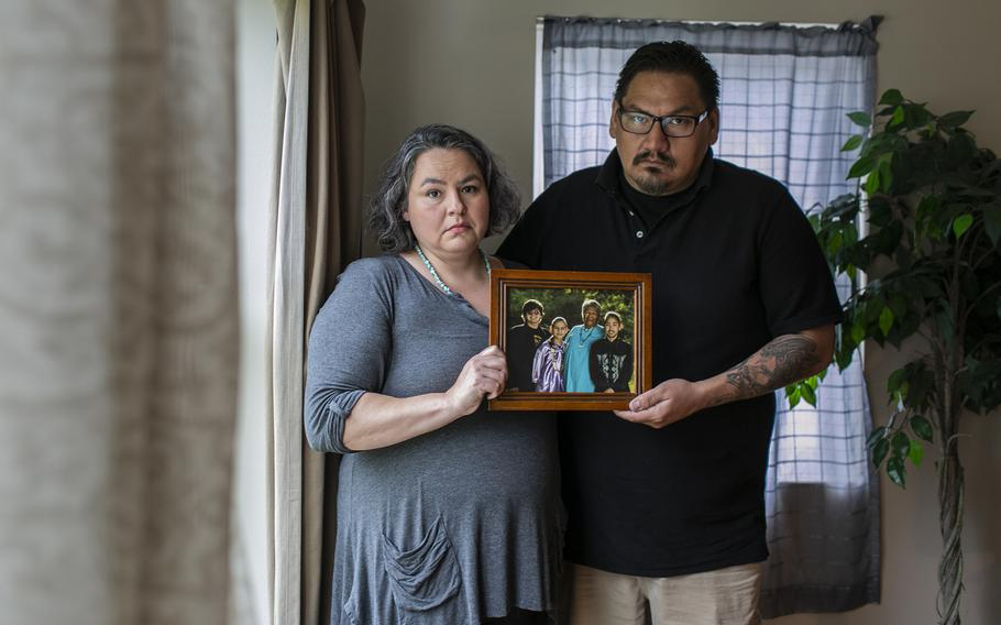 Amanda and her brother, Shane Steindorf, hold a family photo that their mother is in.
