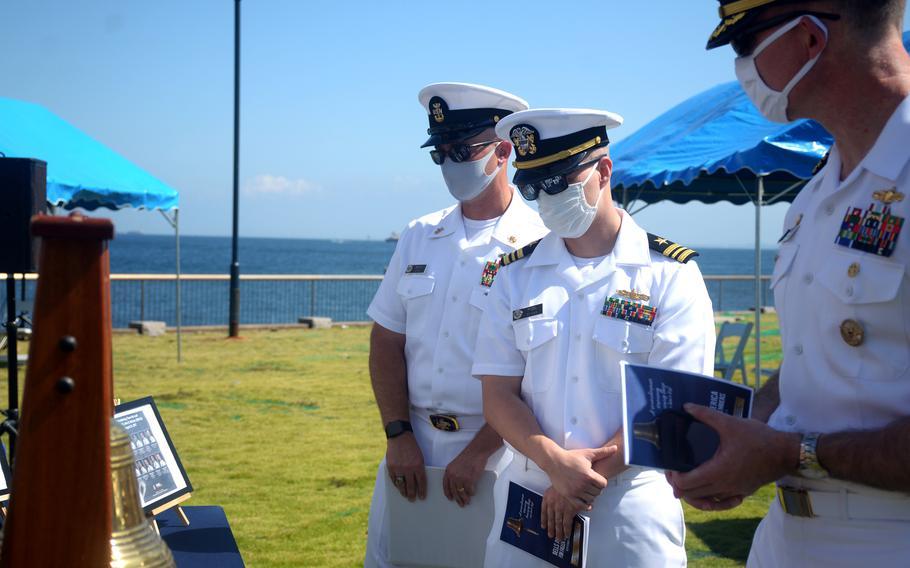 Leaders at Yokosuka Naval Base, Japan, including installation commander Capt. Rich Jarrett, right, look at photos of fallen sailors during a Bells Across America service, Thursday, Sept. 23, 2021.