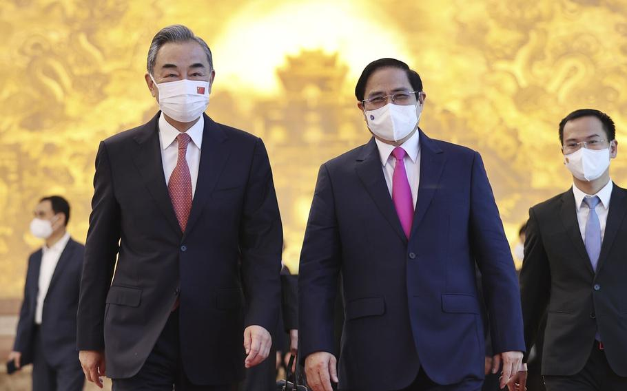 Vietnamese Prime Minister Pham Minh Chinh and Chinese Foreign Minister Wang Yi walk into meeting room in Hanoi, Vietnam, on Saturday, Sept. 11, 2021.