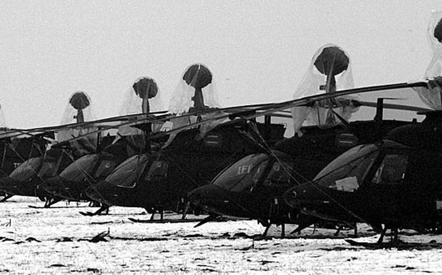 Taszar AB, Hungary, January, 1996: A fleet of attack helicopters rest on a snow covered field at Taszar AB.