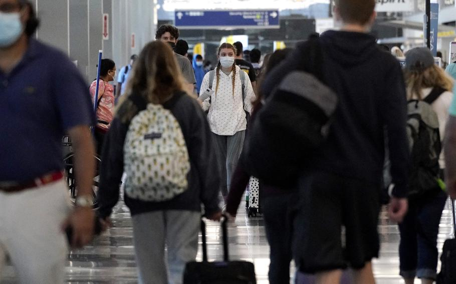 Travelers walk in Terminal 3 at at Chicago's O'Hare International Airport ahead of the Fourth of July weekend, Friday, July 2, 2021.