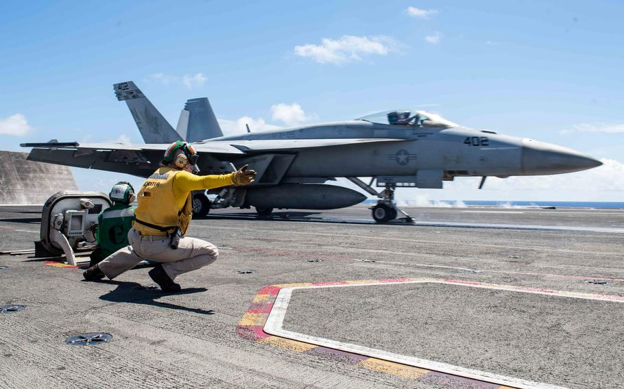U.S. Navy Lt. Kristin Hope signals to launch an F/A-18E Super Hornet from Strike Fighter Squadron (VFA) 195 from the flight deck of the USS Ronald Reagan (CVN 76) during flight operations in the East China Sea, Aug. 22, 2019.