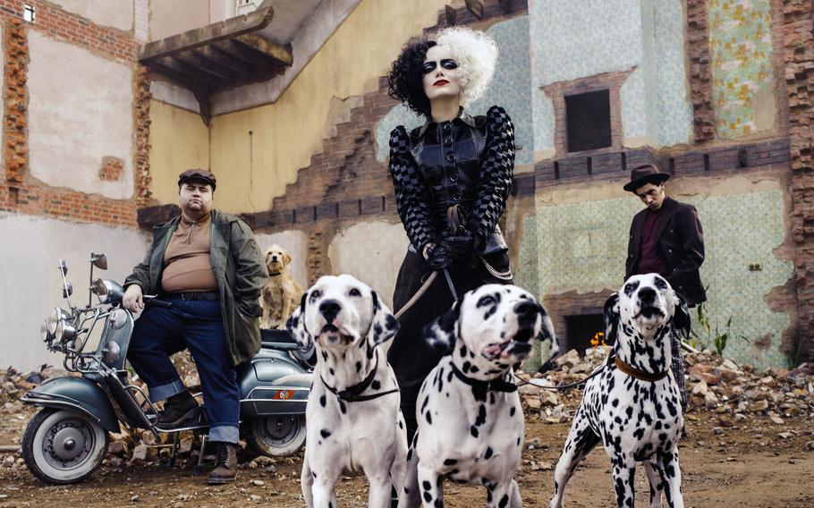 """This image released by Disney shows Paul Walter Hauser, from left, Emma Stone and Joel Fry in a scene from """"Cruella."""""""