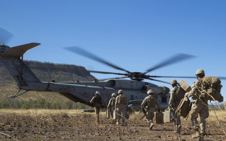 Marines assigned to the 1st Battalion, 5th Marine Regiment rush aboard a CH-53E Super Stallion during Exercise Koolendong in Australia's Northern Territory, Aug. 16, 2021.