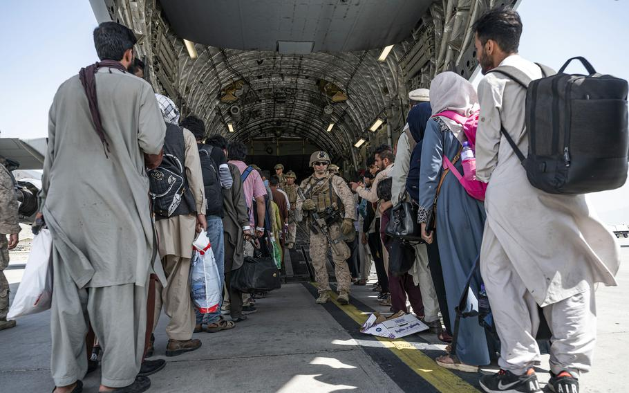 U.S. airmen and Marines guide evacuees aboard a C-17 Globemaster III at Hamid Karzai International Airport in Kabul, Afghanistan, Aug. 21, 2021.