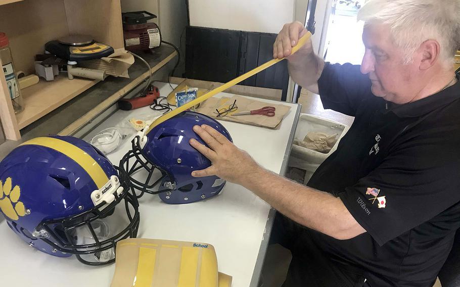 YokotaのTim PujolコーチはチームのヘルメットにPanther前足と黄色の縞模様のデカールを適用します。