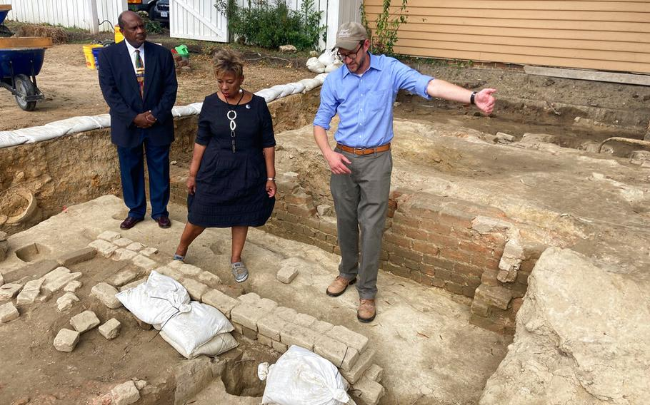 Reginald F. Davis, from left, pastor of First Baptist Church in Williamsburg, Connie Matthews Harshaw, a member of First Baptist, and Jack Gary, Colonial Williamsburg's director of archaeology, stand at the brick-and-mortar foundation of one the oldest Black churches in the U.S. on Wednesday, Oct. 6, 2021, in Williamsburg, Va. Colonial Williamsburg announced Thursday Oct. 7, that the foundation had been unearthed by archeologists.
