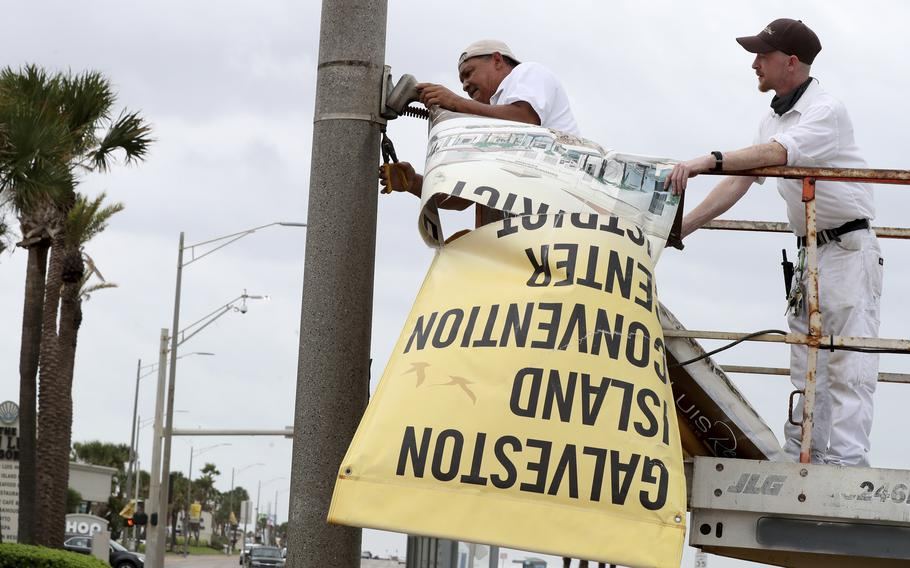 Workers remove banners from a post in front of Landry's Seafood House in Galveston, Texas, Monday, Sept. 13, 2021, as residents and business prepare for Tropical Storm Nicholas.