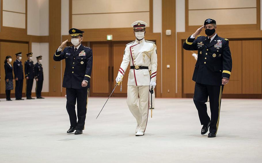 Army Gen. James Dickinson, far right, who oversees U.S. Space Command, reviews Japanese troops during a visit to the Ministry of Defense in Tokyo, Friday, May 21, 2021.