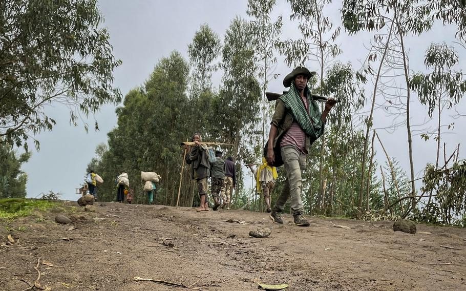 An unidentified armed militia fighter walks down a path as villagers flee with their belongings in the other direction, near the village of Chenna Teklehaymanot, in the Amhara region of northern Ethiopia Thursday, Sept. 9, 2021.