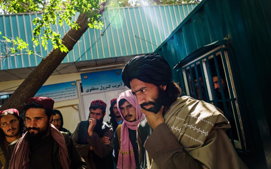 Mawlawi Shaker, far right, the new chief of this city's Police District 10, listens to the plight of a passerby at PD10, in Kabul, Afghanistan, on Sept. 2, 2021.