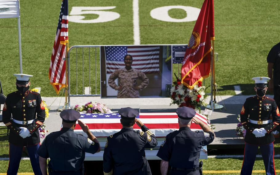 Law enforcement members salute the casket of Sgt. Johanny Rosario Pichardo, a U.S. Marine who was among 13 service members killed in a suicide bombing in Afghanistan, during a public wake at Veterans Memorial Stadium in her hometown of Lawrence, Mass., Tuesday, Sept. 14, 2021.