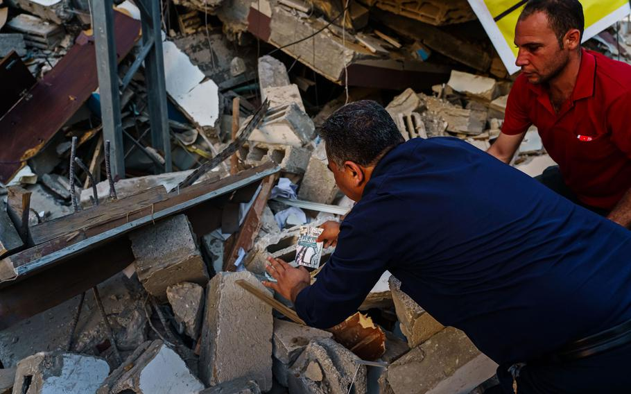 Samir Mansour gathers books from the rubble that was once his bookstore, a Gaza cultural lodestar, destroyed in an Israeli bombardment during the last escalation, which lasted 11 days between Israel and Gaza military factions, in Gaza City on Wednesday, May 26, 2021.