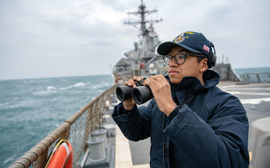 Seaman Xi Chan stands lookout on the USS Barry's flight deck as the guided-missile destroyer passes through the Taiwan Strait in April 2020.