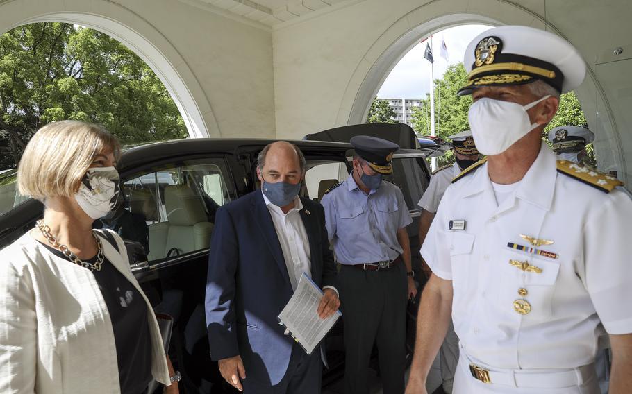 The U.S. 7th Fleet commander, Vice. Adm. Karl Thomas, greets the United Kingdom's Secretary of State for Defence Ben Wallace and Ambassador to Japan Julia Longbottom at Yokosuka Naval Base, Japan, Wednesday, July 21, 2021.