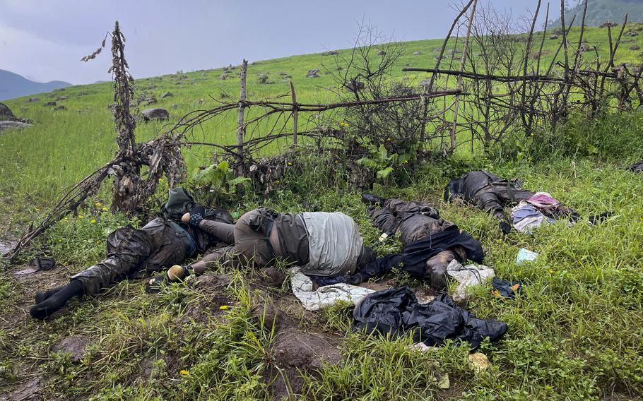 The dead bodies of unidentified people wearing military uniforms lie on the ground near the village of Chenna Teklehaymanot, in the Amhara region of northern Ethiopia on Thursday, Sept. 9, 2021.