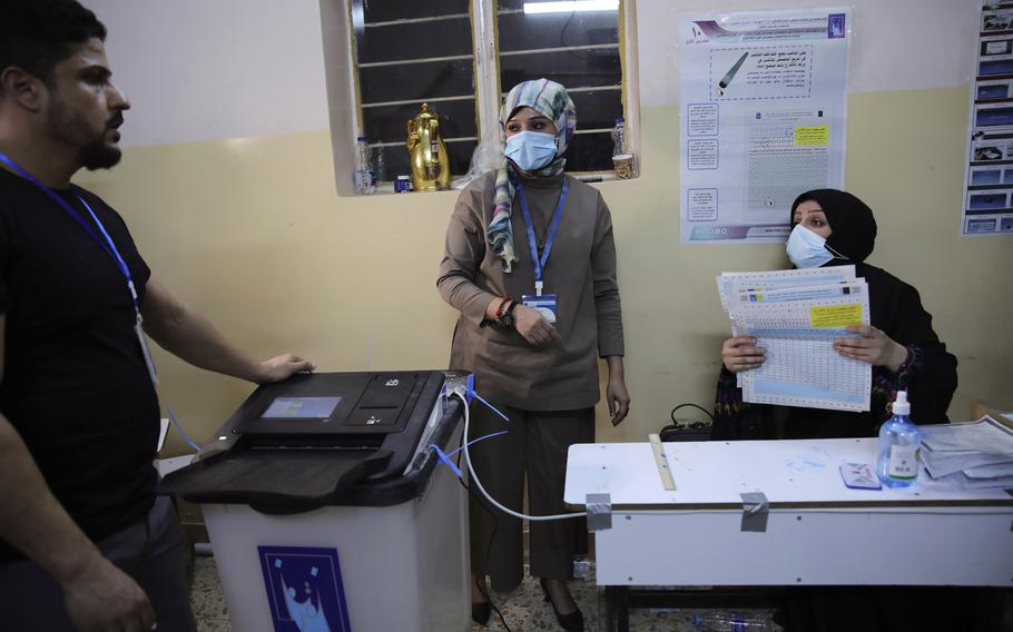 Employees of the Independent High Electoral Commission close the polling center after the end of early voting by the security forces in Basra, Iraq, Friday, Oct. 8, 2021.