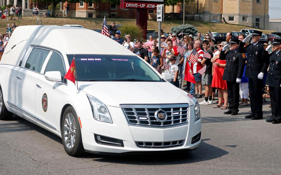 """A hearse carrying the body of Marine Corps Cpl. Humberto """"Bert"""" Sanchez pauses during his funeral procession at the corner of 8th Street and East Market Street on Sept. 12, 2021, in Logansport, Ind."""