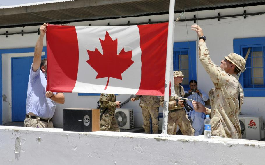 The Canadian flag is lowered for the last time on Camp Nathan Smith in Kandahar City, Afghanistan, June 22, 2011.