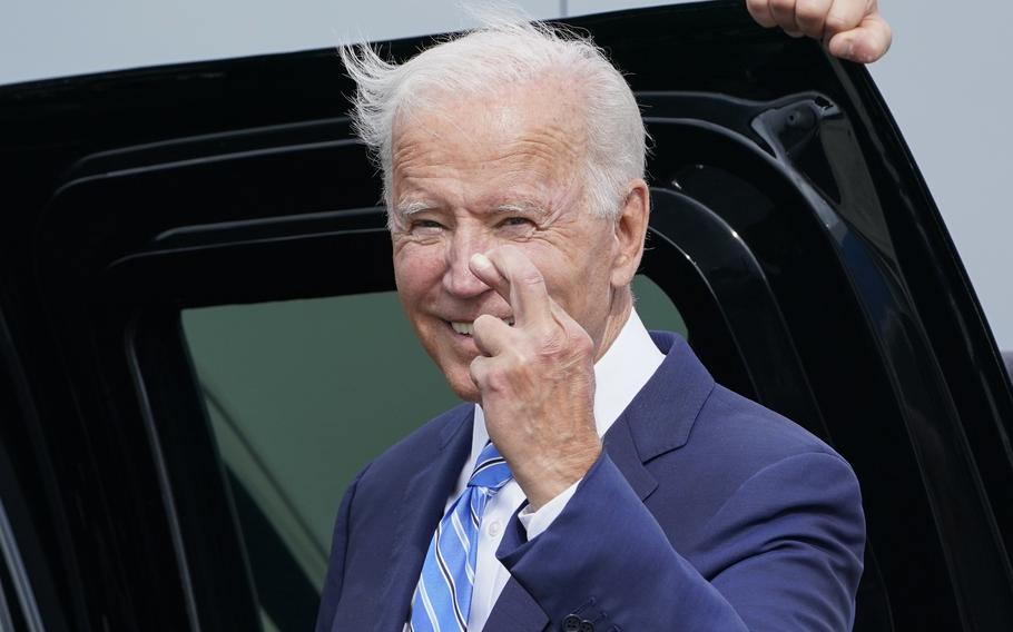 President Joe Biden crosses his fingers as he responds to a question about the short term debt deal as he arrives Air Force One at O'Hare International Airport in Chicago, Thursday, Oct. 7, 2021. While in the Chicago area, Biden will highlight his order to require large employers to mandate COVID-19 vaccines for its workers during a visit to a construction site.