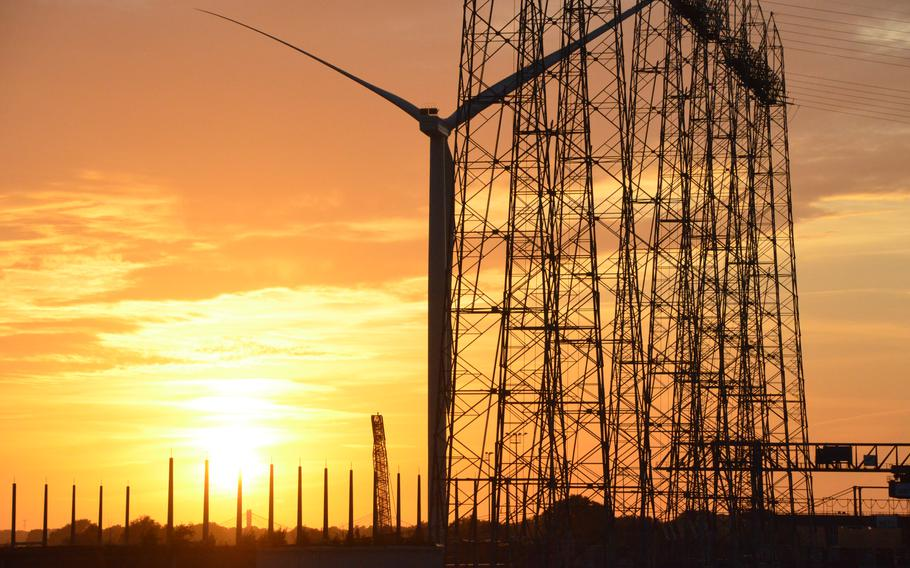 The sun sets over an industrial sector of Nijmegen, the Netherlands, on Aug. 13, 2021. Every evening at sunset, a veteran walks across the Oversteek Bridge.
