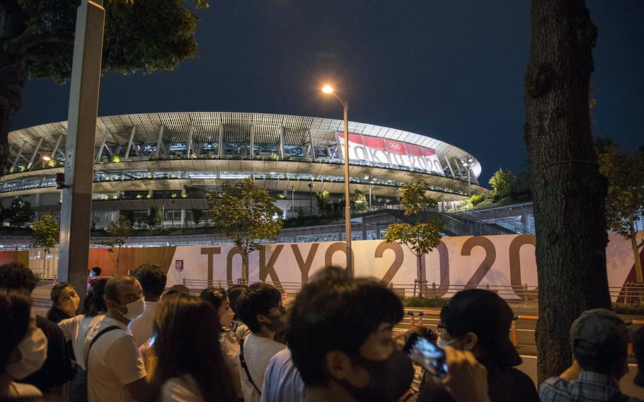 People flock near new National Stadium during the opening ceremony for the Tokyo Olympics, Friday, July 23, 2021.
