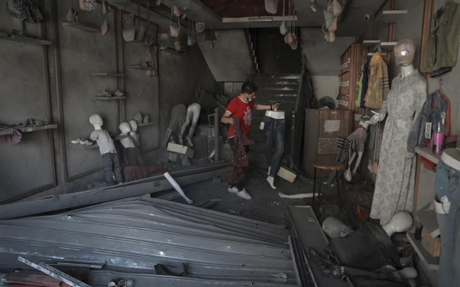 Bilal Mansour surveys his bombed-out Gaza City shop on Sunday, May 23, 2021.