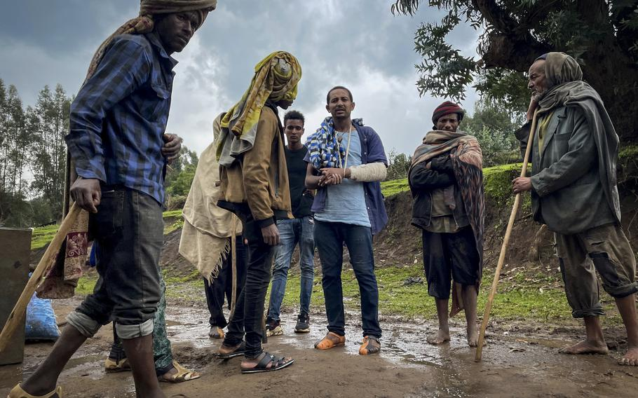 Men gather to speak to a militia fighter Kibret Bidere, with an injured arm, center, near the village of Chenna Teklehaymanot, in the Amhara region of northern Ethiopia Thursday, Sept. 9, 2021.