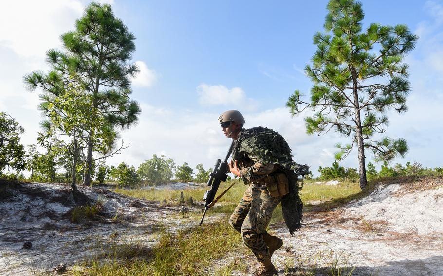 A Marine infantry student at Camp Lejeune, N.C., practices setting up an ambush in a live-fire training event Aug. 27, 2021, during their 12th week of initial infantry training as part of a pilot program meant to drastically change the way the Corps trains its infantrymen. The pilot program expands infantry training from nine to 14 weeks and places Marines in 14-person squads under a single instructor.