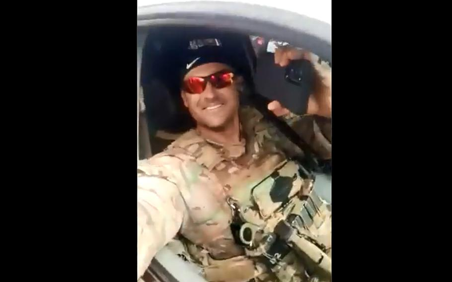 In a screenshot from a Twitter video, a Green Beret smiles at the crowd as Guinean troops escort the U.S. Africa Command team to the U.S. Embassy in the country.