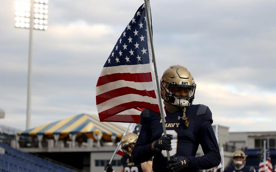 Navy's Cameron Kinley carries a U.S. flag as the team takes the field against Tulsa at Navy-Marine Corps Memorial Stadium on December 5, 2020, in Annapolis, Maryland.