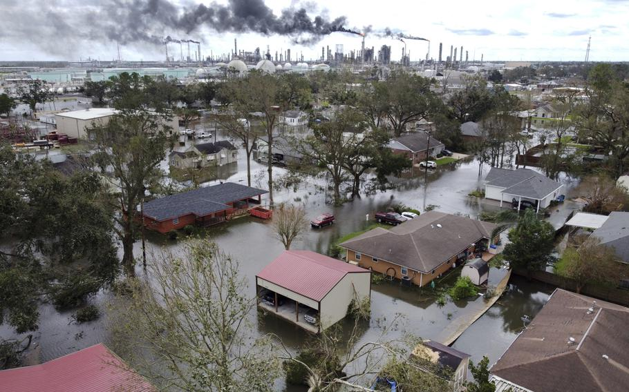 Homes near Norco, La., are surrounded by floodwater as chemical refineries continue to flare the day after Hurricane Ida hit southern Louisiana, Monday, Aug. 30, 2021.