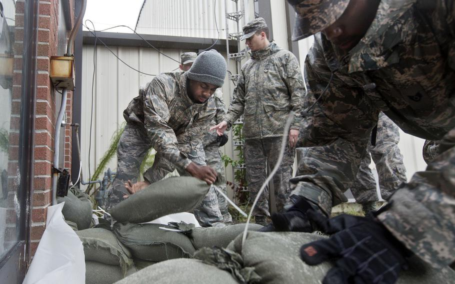 Airmen and volunteers place sandbags as heavy rain falls outside of a building at Langley Air Force Base in preparation for Hurricane Joaquin in October 2015.