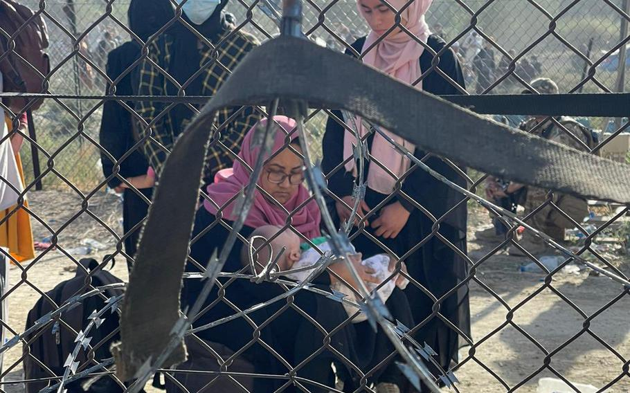 Afghan women tend to a baby in an undated photo taken through a chain link fence at Kabul, Afghanistan's international airport. While an evacuation effort brought more than 123,000 civilians from the country on U.S. and coalition aircraft, not everyone the U.S. wanted to evacuate was able to leave, said Marine Gen. Frank McKenzie, head of U.S. Central Command, on Aug. 30, 2021.