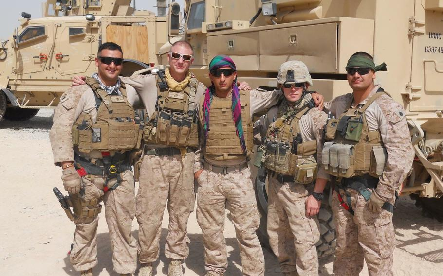 Mohammad Nadir, center, poses with Marines in Helmand province, Afghanistan, in 2017. Nadir served as an interpreter for nearly three years before applying for a U.S. Special Immigrant Visa. Nadir later enlisted in the Marine Corps.