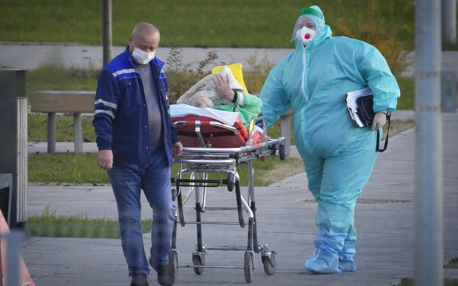 Medical workers carry a patient suspected of having coronavirus on a stretcher at a hospital in Kommunarka, outside Moscow, Russia, Monday, Oct. 11, 2021. Russia's daily coronavirus infections and deaths are hovering near all-time highs amid a laggard vaccination rate and the Kremlin's reluctance to toughen restrictions. Russia's state coronavirus task force reported 29,409 new confirmed cases Monday. That's the highest number since the start of the year and just slightly lower than the pandemic record reached in December.