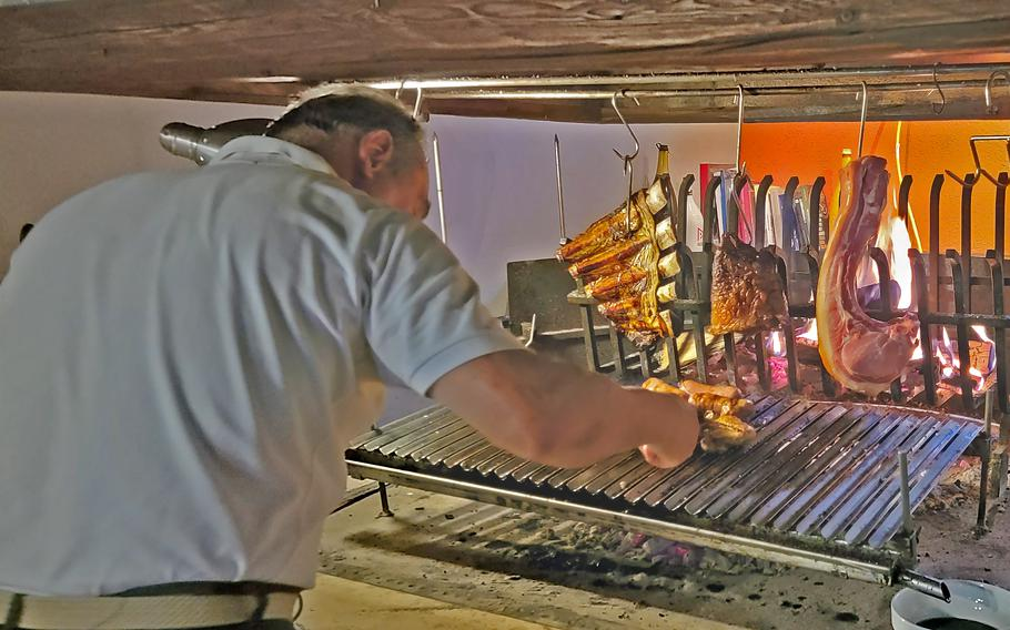 Jose Polesello, owner of Osteria El Gaucho, in Mansue, Italy, which is about a 30-minute drive from Aviano Air Base, rotates his slowly grilled meats.